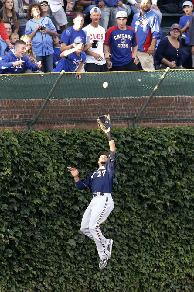 Photo - Milwaukee Brewers center fielder Carlos Gomez makes a leaping catch on a fly ball hit by Chicago Cubs' Javier Baez at the ivy in left center field, during the first inning of a baseball game Tuesday, Aug. 12, 2014, in Chicago. (AP Photo/Charles Rex Arbogast)