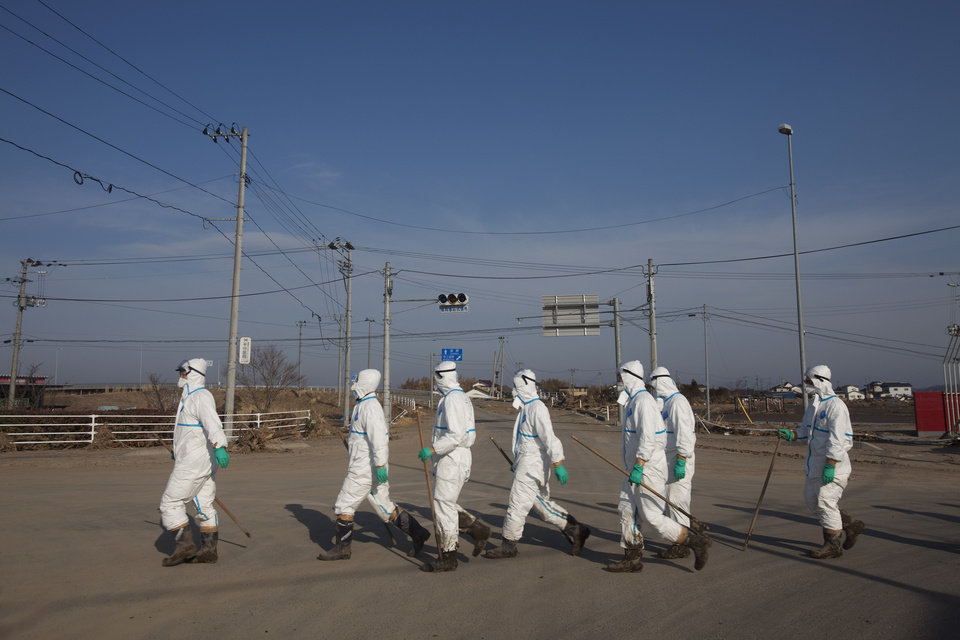 "FILE - In this April 7, 2011 file photo, Japanese police wearing protective radiation suits search for the bodies of victims of the tsunami in the Odaka area of Minami Soma, inside the deserted evacuation zone established for the 20-kilometer radius around the Fukushima Dai-ichi nuclear power plants. Japanese film director Yojyu Matsubayashi took a more standard documentary approach for his ""Fukushima: Memories of the Lost Landscape,"" interviewing people who were displaced in the Fukushima town of Minami Soma. He followed them into temporary shelters in cluttered gymnasiums and accompanied their harried visits to abandoned homes with the gentle patience of a video-journalist. The March 2011 catastrophe in Japan has set off a flurry of independent films telling the stories of regular people who became overnight victims, stories the creators feel are being ignored by mainstream media and often silenced by the authorities. (AP Photo/David Guttenfelder, File)"