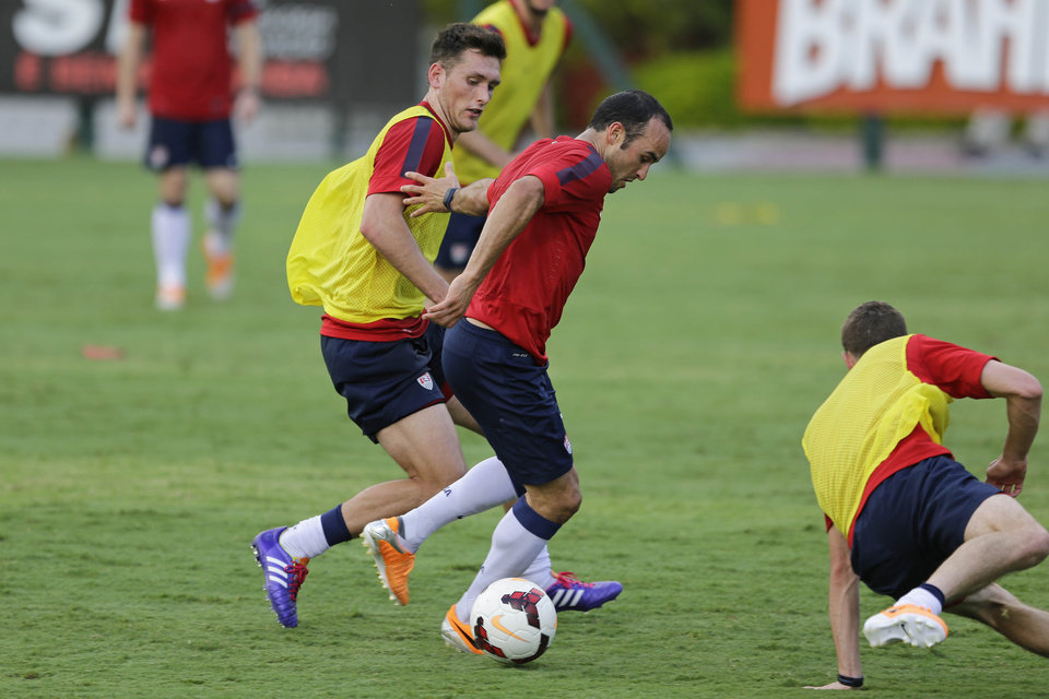 Photo - United States' Landon Donavan fights for the ball with Matt Besler, left, during a training session in Sao Paulo, Brazil, Tuesday, Jan. 14, 2014. The US national soccer team is on a 10-day training program in Sao Paulo preparing for the World Cup tournament, which gets underway on June 12. (AP Photo/Nelson Antoine)