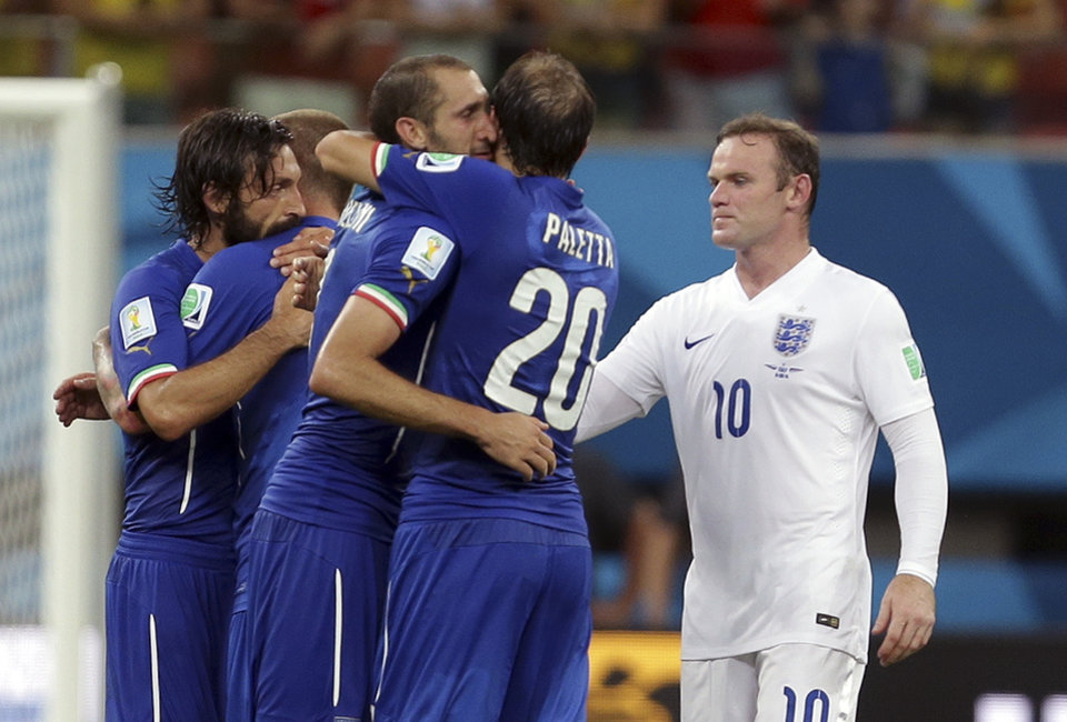 Photo - England's Wayne Rooney, right, looks on as Italy's Gabriel Paletta, center, and other Italian players celebrate after the group D World Cup soccer match between England and Italy at the Arena da Amazonia in Manaus, Brazil, Saturday, June 14, 2014. Italy won the match 2-1.  (AP Photo/Martin Mejia)