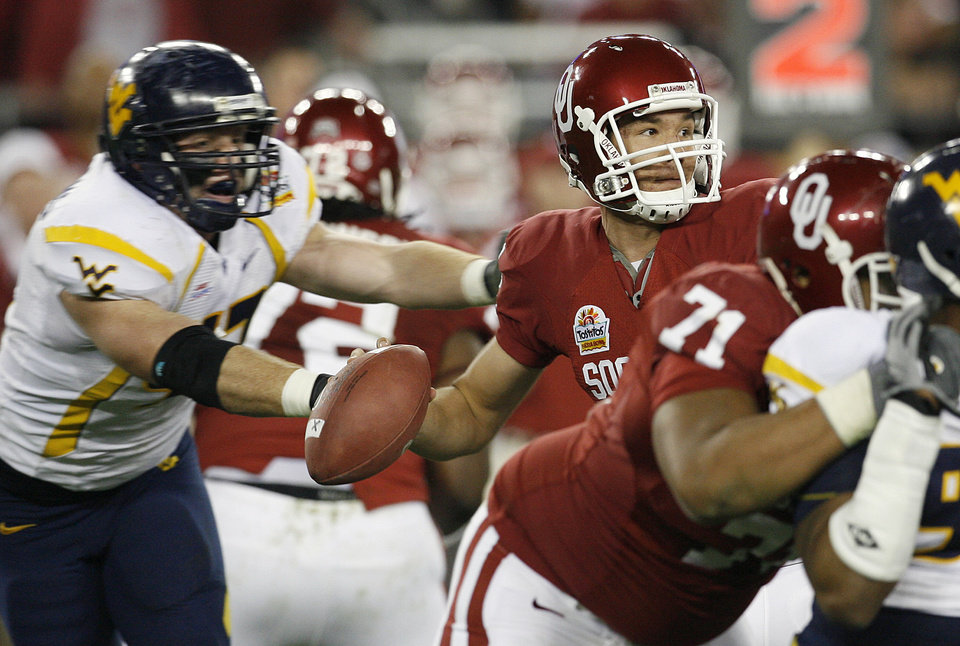 Photo - West Virginia's Reed Williams (47) puts pressure on Oklahoma Sam Bradford (14) during the first half of the Fiesta Bowl college football game between the University of Oklahoma Sooners (OU) and the West Virginia University Mountaineers (WVU) at The University of Phoenix Stadium on Wednesday, Jan. 2, 2008, in Glendale, Ariz. 