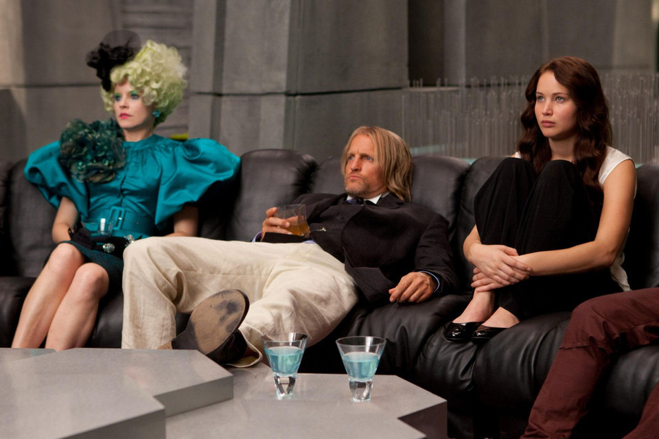 "Effie Trinket (Elizabeth Banks, left), Haymitch Abernathy (Woody Harrelson, center) and Katniss Everdeen (Jennifer Lawrence, right) in ""The Hunger Games."" PHOTO BY MURRAY CLOSE PROVIDED. <strong>Photo credit: Murray Close</strong>"
