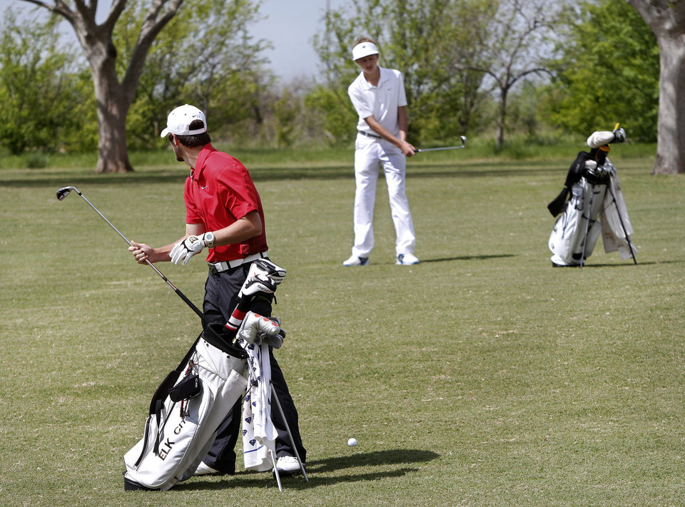 Elk City golfer  Berek Dyson, foreground,  makes his club selection while Heritage Hall's Sam Jackson takes practice swing on the fairway as this threesome waits for golfers ahead to finish play during Class 4A boy's state golf  tournament on Tuesday, May 7, 2013,  at  Hefner Golf Course in Oklahoma City.   Photo  by Jim Beckel, The Oklahoman.