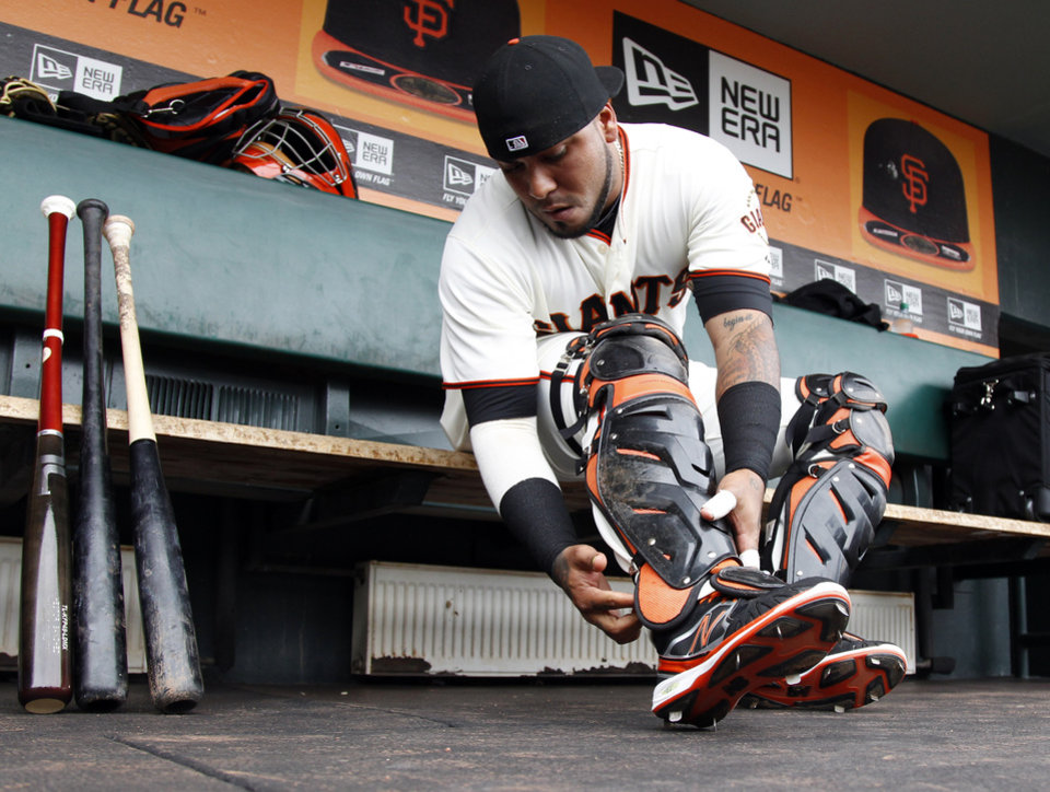 Photo - San Francisco Giants catcher Hector Sanchez straps on his gear in preparation for  a baseball game against the Miami Marlins on Saturday, May 17, 2014, in San Francisco. (AP Photo/Marcio Jose Sanchez)