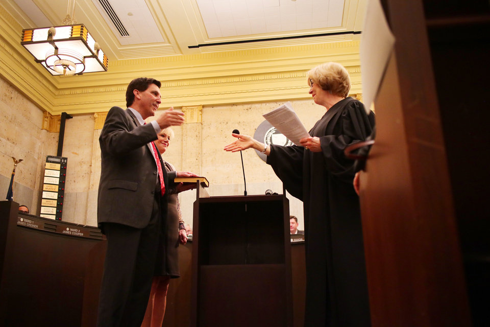 Photo - Oklahoma Supreme Court Justice Noma Gurich swears in Mark Stonecipher as his wife, Debbie, holds the Bible, ward 8, during the swearing in ceremony for the Oklahoma City Council, Tuesday, April 9, 2019.  Photo by Doug Hoke/The Oklahoman