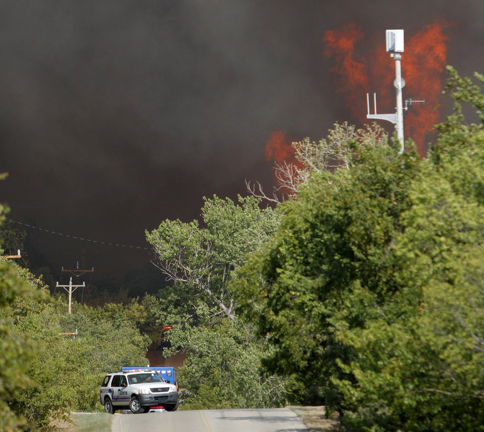 Photo - Emergency vehicles drive down NW 122nd street near Midwest Blvd as flames from a wildfire approach in Oklahoma City, Wednesday, August 31, 2011. Photo by Bryan Terry, The Oklahoman