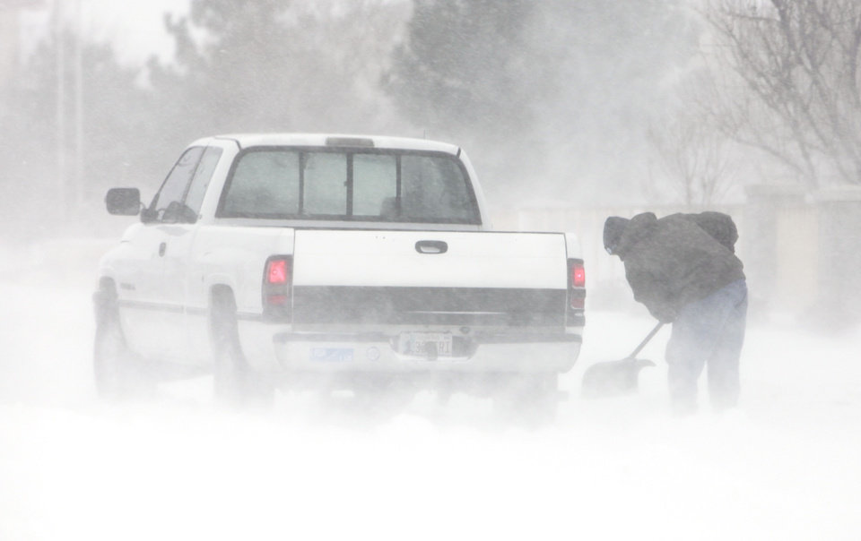 Photo - A stranded motorist tries to dig out his truck on 15th just west of Broadway in Edmond, Tuesday, February 1, 2011.        Photo by David McDaniel, The Oklahoman
