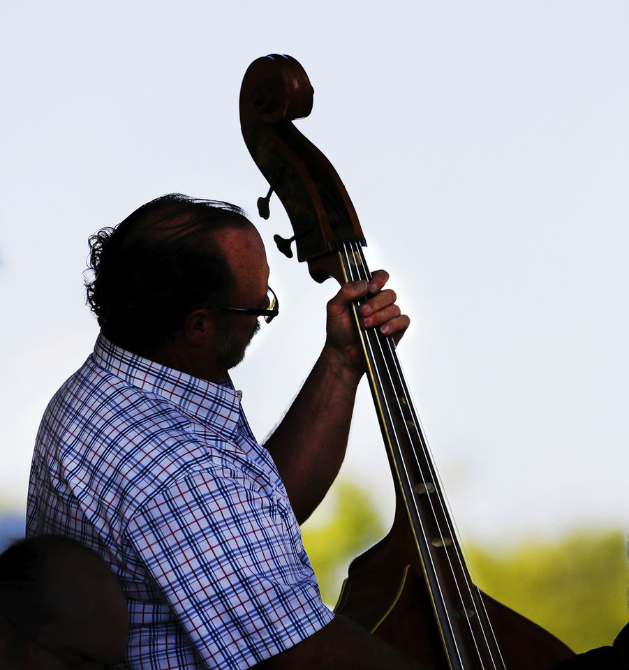 Photo - Mike Perry plays bass fiddle with other musicians during an afternoon session at the 17th annual Oklahoma's International Bluegrass Festival in Cottonwood Flats Municipal Park in Guthrie on Thursday, Oct. 3, 2013.   Photo  by Jim Beckel, The Oklahoman.  The event, which features bluegrass bands and musicians from around the world, continues daily through Saturday, Oct. 5.