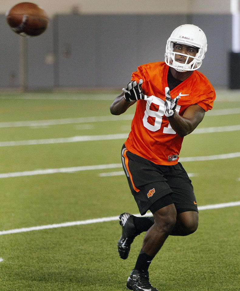 Photo - Oklahoma State wide receiver Jhajuan Seales (81) catches a ball during the first team practice of the fall at the Sherman E. Smith Training Facility on the campus of Oklahoma State University in Stillwater on August 1, 2014. Photo by KT King, The Oklahoman