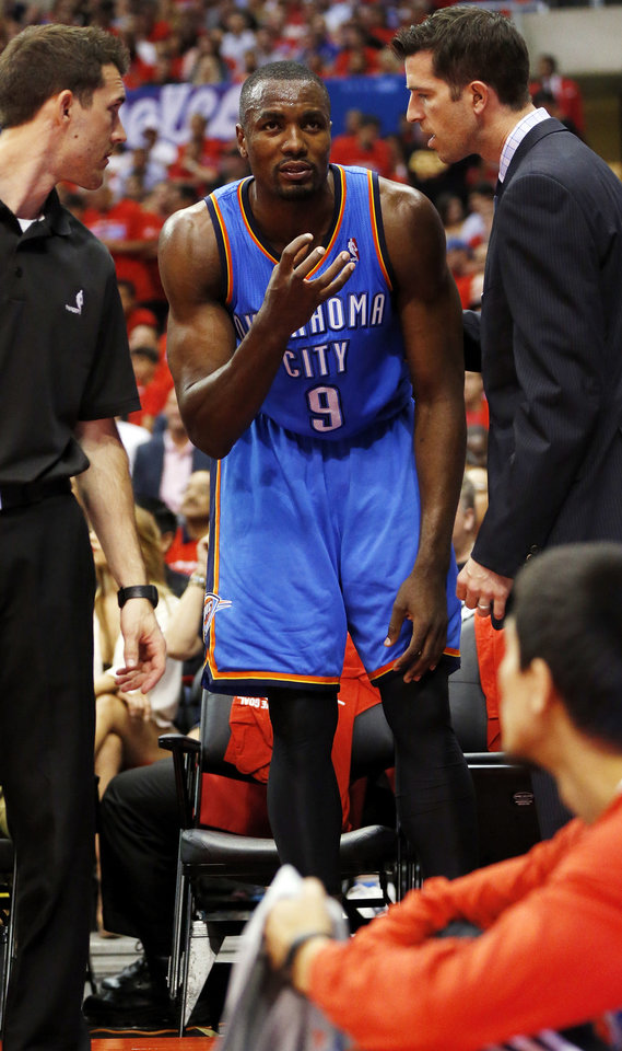 Thunder forward Serge Ibaka talks with the Thunder staff before leaving the floor after injuring his calf during Thursday night's Game 6 against the Clippers. Photo by Nate Billings, The Oklahoman