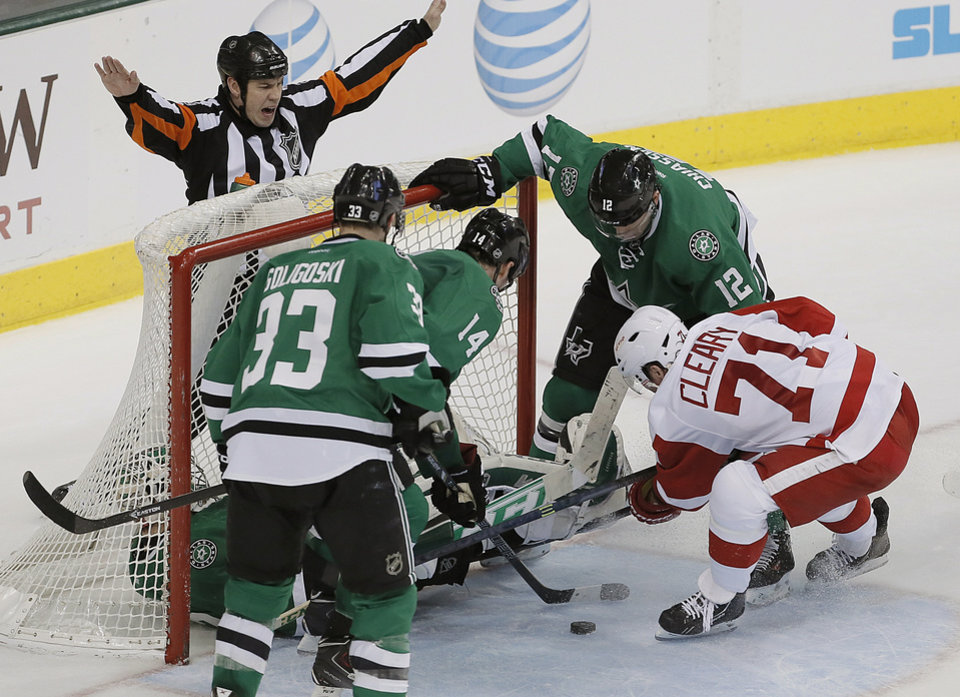 Detroit Red Wings forward Daniel Cleary (71) attempts to score on a rebound as Dallas Stars defenseman Alex Goligoski (33), forwards Jamie Benn (14) and Alex Chiasson (12) and goalie Kari Lehtonen (32) defend in the second period of an NHL hockey game, Saturday, Jan. 4, 2014, in Dallas. (AP Photo/Brandon Wade)