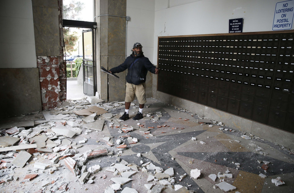 Photo - Jorge Sanchez looks over damage to the main post office following an earthquake Sunday, Aug. 24, 2014, in Napa, Calif. A large earthquake caused significant damage in California's northern Bay Area early Sunday, sending at least 70 people to a hospital, igniting fires, knocking out power to tens of thousands and sending residents running out of their homes in the darkness. (AP Photo/Eric Risberg)