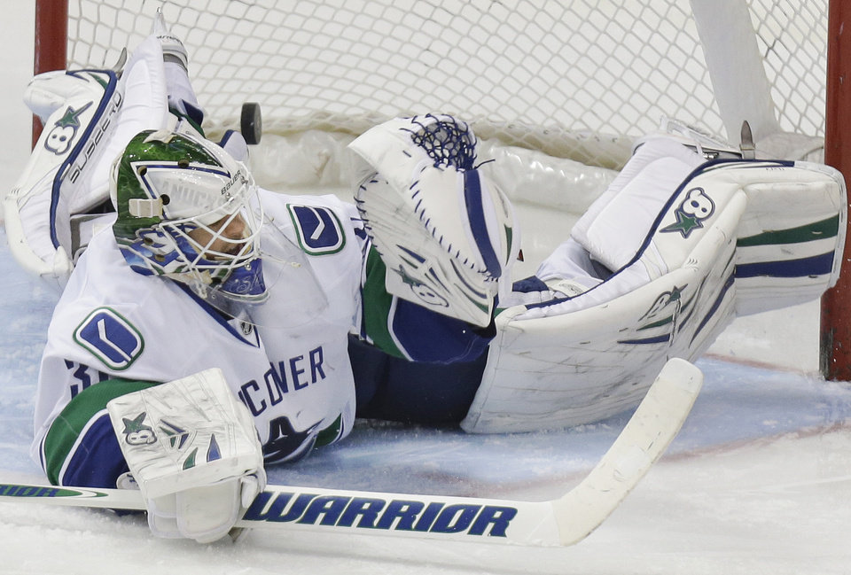 Photo - Vancouver Canucks goalie Eddie Lack (31) can't stop the puck allowing a goal shot by Dallas Stars Alex Goligoski, not shown, during the second period of an NHL hockey game Thursday, March 6, 2014, in Dallas. (AP Photo/LM Otero)