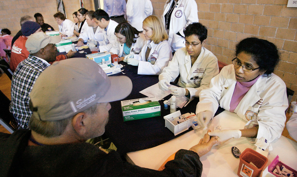 Photo - OU College of Pharmacy students test blood sugar levels during a health fair at the City Rescue Mission. PHOTO BY Jim Beckel, The Oklahoman