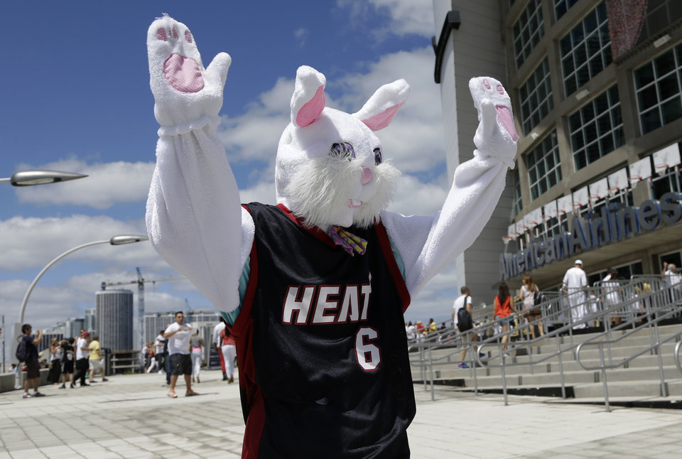 Photo - A person dressed as the Easter Bunny wears a LeBron James jersey and waves to fans as they arrive for Game 1 of an opening-round NBA basketball playoff series between the Miami Heat and the Charlotte Bobcats, Sunday, April 20, 2014, in Miami. (AP Photo/Lynne Sladky)
