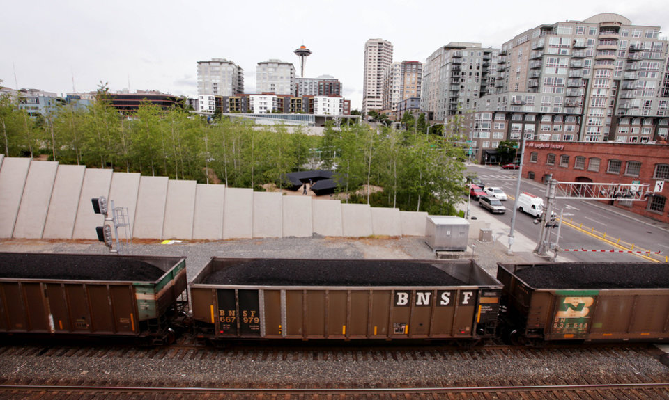 Photo - FILE - In this May, 29, 2012, file photo, a train hauling coal from an Arch Coal Inc. mine in the Powder River basin of Montana and Wyoming heads north out of downtown Seattle. A 10 percent reduction in carbon dioxide emissions will mean a decline of 180 million tons, or 18 percent, in U.S. coal production, according to Bernstein Research. That would hurt miners such as Peabody Energy, Alpha Natural Resources and Arch Coal.  (AP Photo/Elaine Thompson, File)
