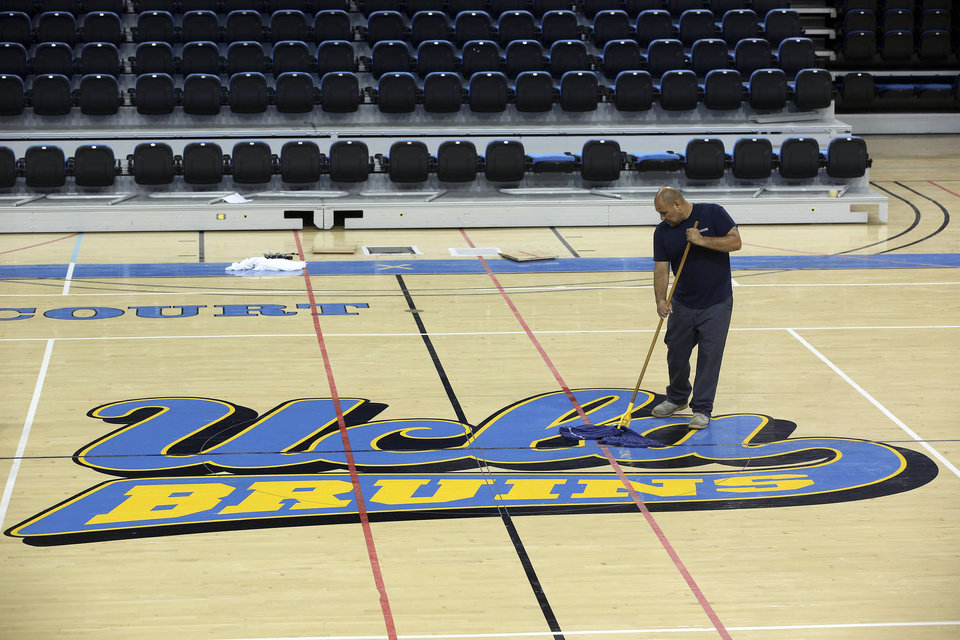 Photo - Worker Ruben Monter mops up the floor at Pauley Pavillion Wednesday July 30, 2014 in Los Angeles. A ruptured 93-year-old water main on Tuesday left the UCLA campus awash in 8 million gallons of water in the middle of California's worst drought in decades, stranding people in parking garages and flooding the school's storied basketball court less than two years after a major renovation.  (AP Photo/ Nick Ut)