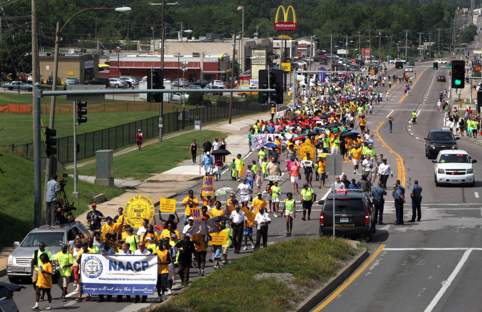 Photo - Members of the St. Louis chapters of the NAACP and the National Urban League march on West Florissant Avenue in Ferguson, Mo., on Saturday, Aug. 23, 2014. Ferguson's streets remained peaceful as tensions between police and protesters continued to subside after nights of violence and unrest that erupted when Officer Darren Wilson, a white police officer, fatally shot Michael Brown, an unarmed black 18-year-old. (AP Photo/St. Louis Post-Dispatch, Robert Cohen)
