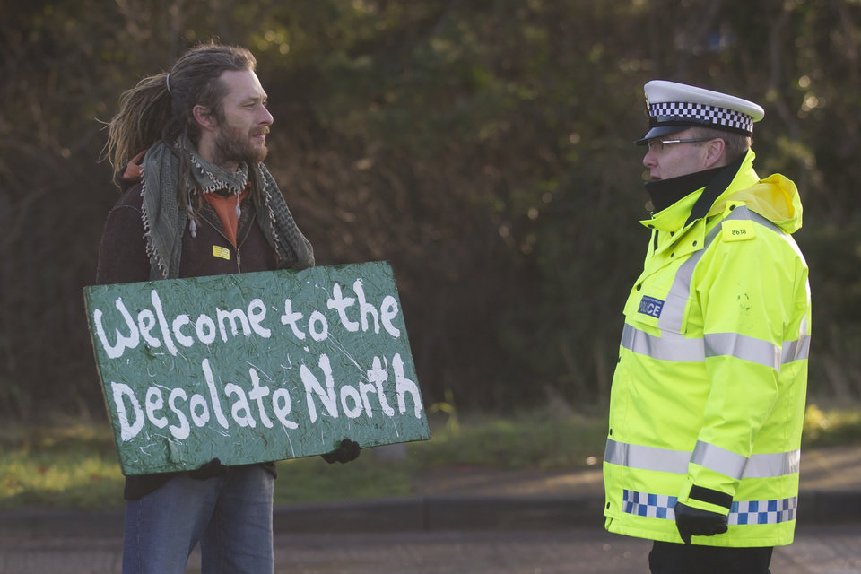 Photo - An anti-fracking protestor stands by a policeman as vehicles attempt to enter an exploratory drill site for the controversial gas extraction process at Barton Moss in Manchester, England, Monday, Jan. 13, 2014.  Councils that back