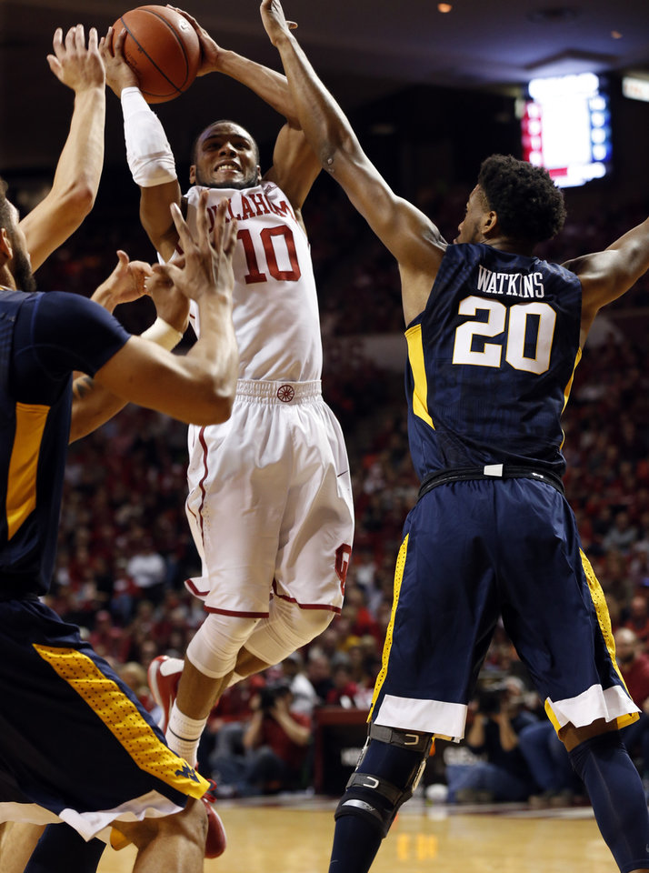 Photo - Oklahoma's Jordan Woodard (10) shoots between West Virginia's Esa Ahmad (23) and Brandon Watkins (20) as the University of Oklahoma Sooner (OU) men play the West Virginia Mountaineers (WV) in NCAA, college basketball at The Lloyd Noble Center on Jan. 16, 2016 in Norman, Okla. Photo by Steve Sisney, The Oklahoman