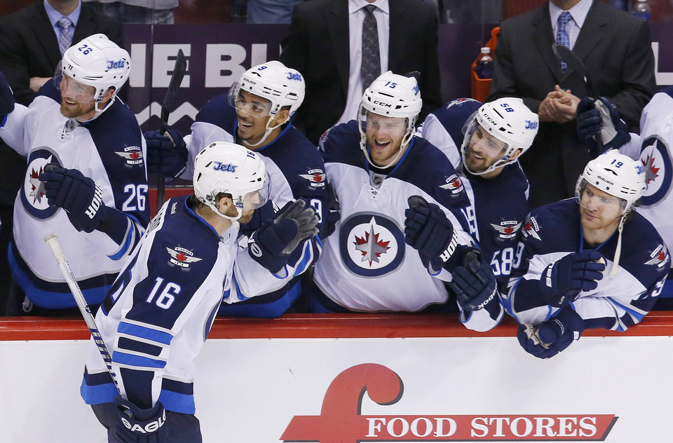 Photo - Winnipeg Jets' Andrew Ladd (16) celebrates his shootout goal against the Phoenix Coyotes with teammates Blake Wheeler (26), Evander Kane (9), Matt Halischuk (15), Eric O'Dell (58) and Jim Slater (19) during an NHL hockey game, Tuesday, April 1, 2014, in Glendale, Ariz. The Jets defeated the Coyotes 2-1. (AP Photo/Ross D. Franklin)