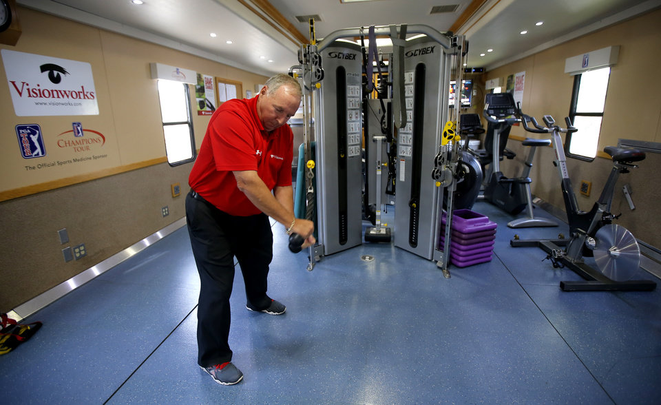 Photo - Certified athletic trainer Kent Biggerstaff demonstrates an exercise inside a training trailer for tour players during the U.S. Senior Open at Oak Tree National in Edmond, Okla., Tuesday, July 8, 2014. Photo by Bryan Terry, The Oklahoman
