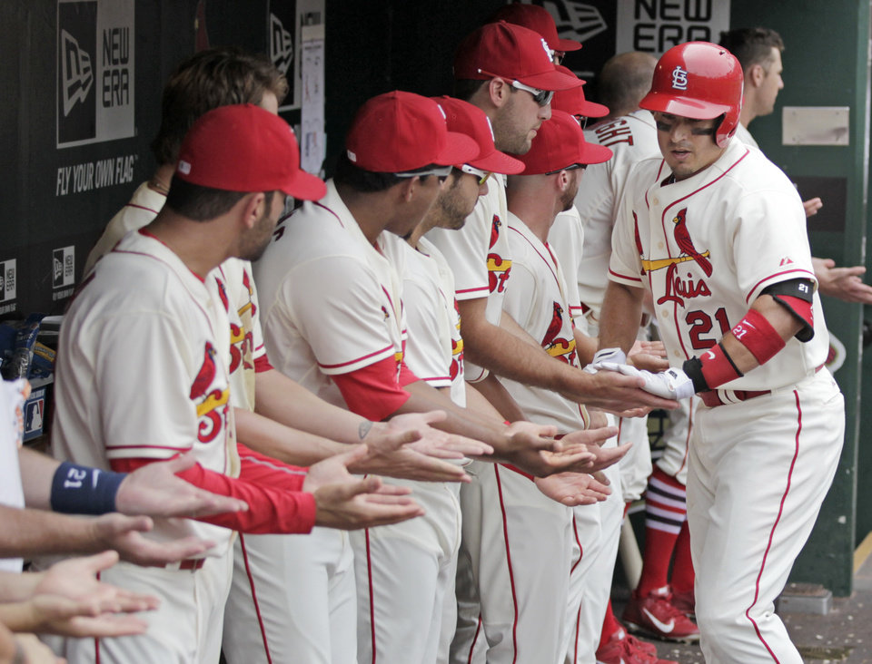 Photo - St. Louis Cardinals' Allen Craig (21) celebrates with teammates in the dugout after hitting a two-run home run in the fourth inning of a baseball game against the Miami Marlins, Saturday, July 5, 2014, in St. Louis.(AP Photo/Tom Gannam)