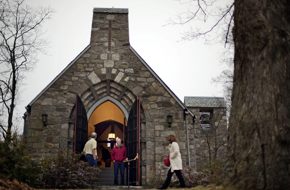 Photo - A churchgoer enters a service at at St John's Episcopal Church, Sunday, Dec. 16, 2012, in Newtown, Conn. A gunman walked into Sandy Hook Elementary School in Newtown Friday and opened fire, killing 26 people, including 20 children. (AP Photo/David Goldman)