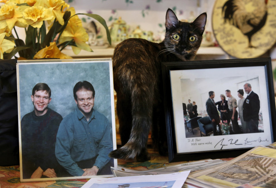 Photo - The Blairs' family cat stands between photos of Thomas A. Blair and Al Blair III. PHOTO BY JIM BECKEL, THE OKLAHOMAN  Jim Beckel