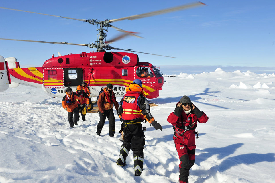 Photo - In this photo provided by China's Xinhua News Agency, the first group of passengers who were aboard the trapped Russian vessel MV Akademik Shokalski, arrive at a safe surface off the Antarctic, Thursday, Jan. 2, 2014.  The helicopter rescued all 52 passengers from the research ship that has been trapped in Antarctic ice, 1,500 nautical miles south of Hobart, Australia, since Christmas Eve after weather conditions finally cleared enough for the operation Thursday. (AP Photo/Xinhua, Zhang Jiansong) NO SALES
