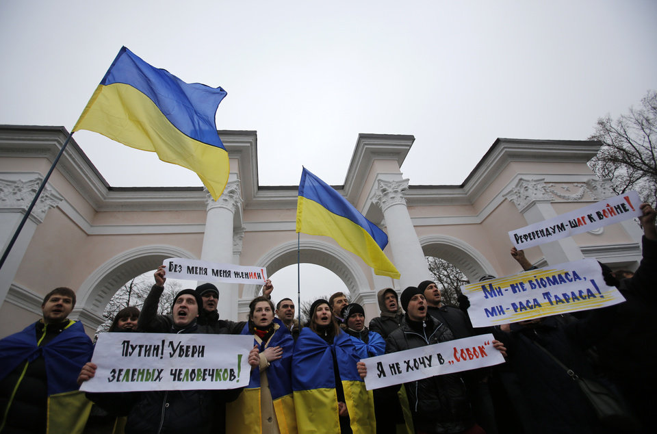 Photo - People hold Ukrainian flags and banners that read: