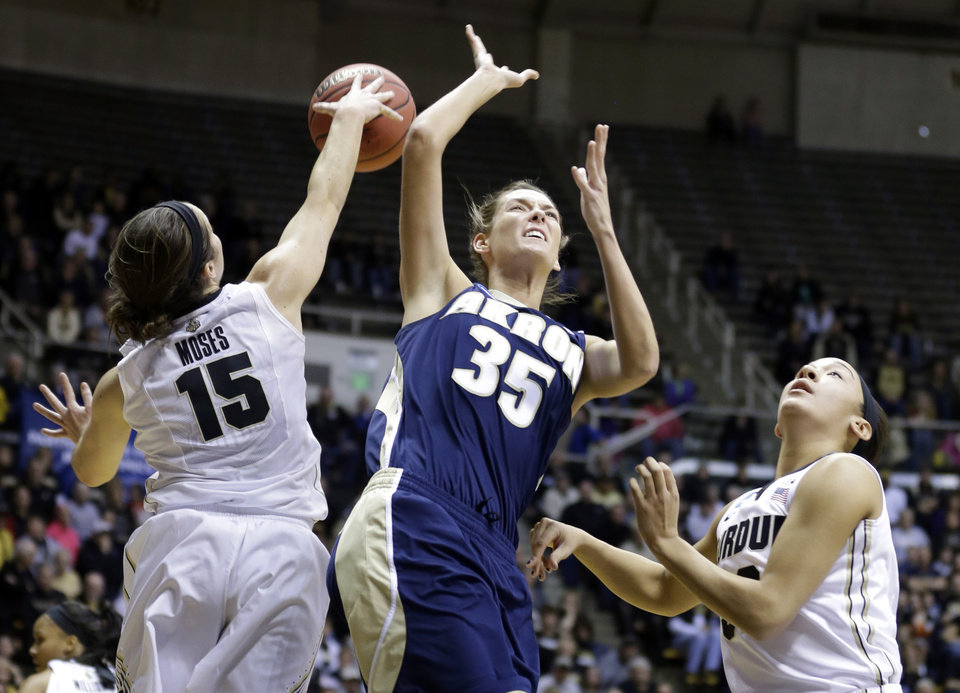 Photo - Akron forward Carly Young (35) has her shot blocked by Purdue guard Courtney Moses (15) as she shoots over Purdue forward Whitney Bays during the first half of a first-round game in the NCAA women's college basketball tournament, Saturday, March 22, 2014, in West Lafayette, Ind. (AP Photo/Michael Conroy)