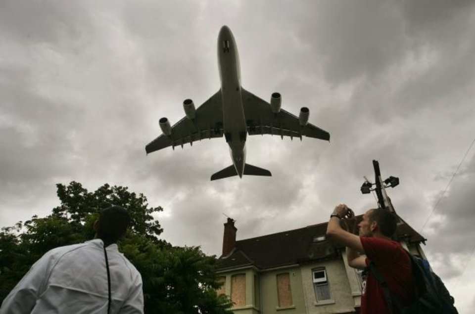 Photo -  An Airbus A-380 approaches to land as locals gather to watch during a flight display at the Farnborough International Airshow in 2008. Air show officials have canceled the industry event, which draws business leaders and governments from across the world. [LEFTERIS PITARAKIS/AP FILE]