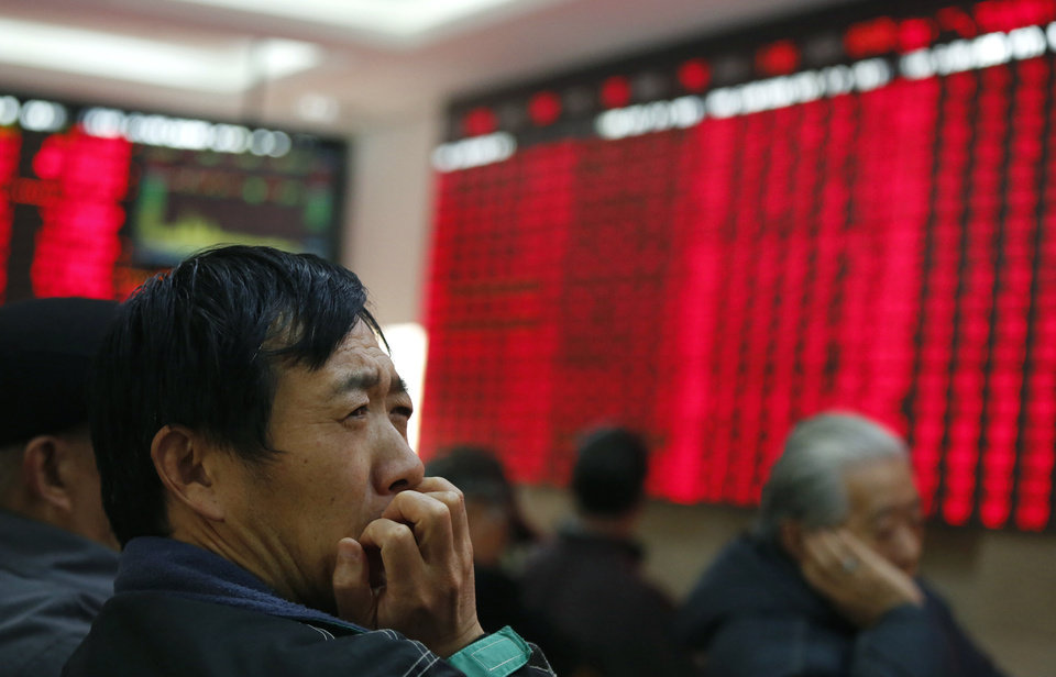 An investor gestures as he looks at the stock price monitor at a private securities company Wednesday, Dec. 5, 2012, in Shanghai, China. Asian stock markets rose Wednesday as investors became increasingly convinced that U.S. political leaders will reach a budget deal that avoids a major hit to the world's No. 1 economy. Chinese shares soared on hopes for more stimulus measures. (AP Photo)