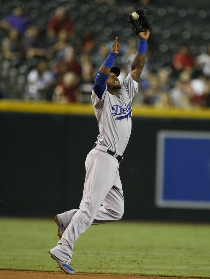 Photo - Los Angeles Dodgers shortstop Hanley Ramirez makes the jumping catch in the fourth inning during a baseball game against the Arizona Diamondbacks, Tuesday, Aug. 26, 2014, in Phoenix. (AP Photo/Rick Scuteri)