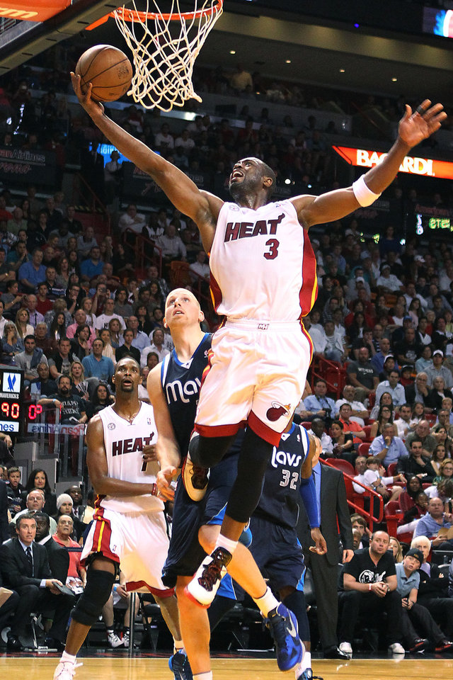 Miami Heat's Dwyane Wade (3) goes to the basket against Dallas Mavericks' Chris Kaman during the fourth quarter of their NBA basketball game, Wednesday, Jan. 2, 2013, in Miami. The Heat won 119-109 in overtime. (AP Photo/El Nuevo Herald, David Santiago)  MAGS OUT