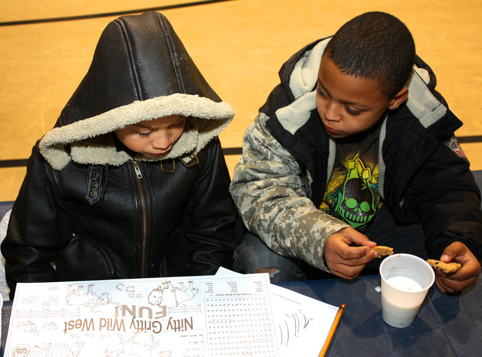 Photo - Brothers Jayden Massey, 9, left, and Casey Massey, 7, work a Christmas word puzzle while having cookies and milk at a candy cane hunt in Norman, sponsored by the city and the Pioneer Library System. PHOTO BY LYNETTE LOBBAN, FOR THE OKLAHOMAN