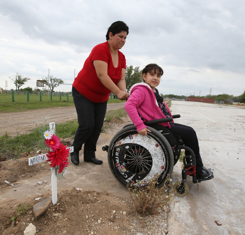 Photo - Mariana Saldivar, 8, right, is wheel by her mother Sandra, left, past a wooden cross in memory of her father Mariano, Thursday, April 17, 2014 in West, Texas. Saldivar  died in the apartment complex destroyed by the fertilizer plant explosion one year ago. Today marks the one-year anniversary of the explosion. (AP Photo/Waco Tribune Herald, Jerry Larson)