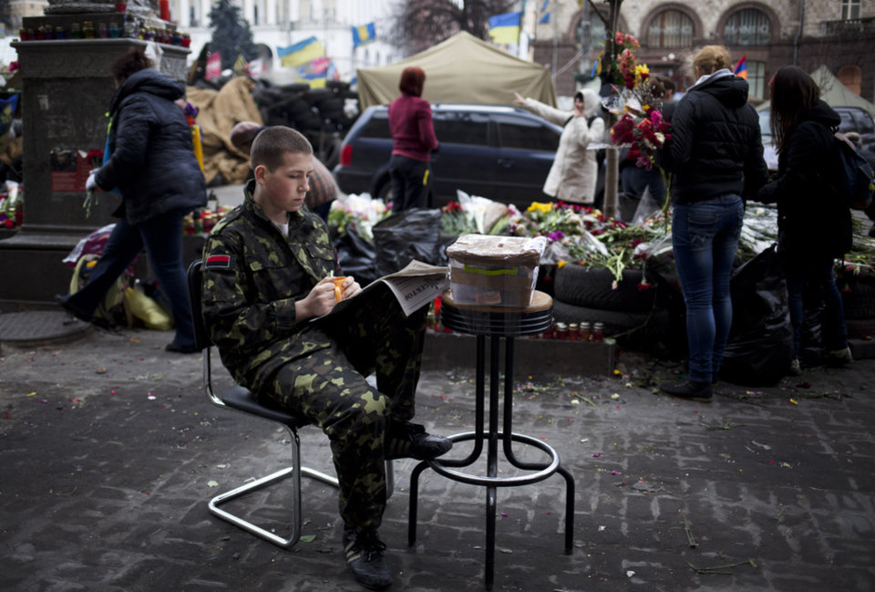Photo - A young Red Sector member sits next to a donation box in Kiev's Independence Square, Ukraine, Sunday, March 16, 2014. In a referendum watched closely around the world, residents in Ukraine's strategic Crimean Peninsula voted Sunday on whether to demand greater autonomy or split off and seek to join Russia. (AP Photo/David Azia)