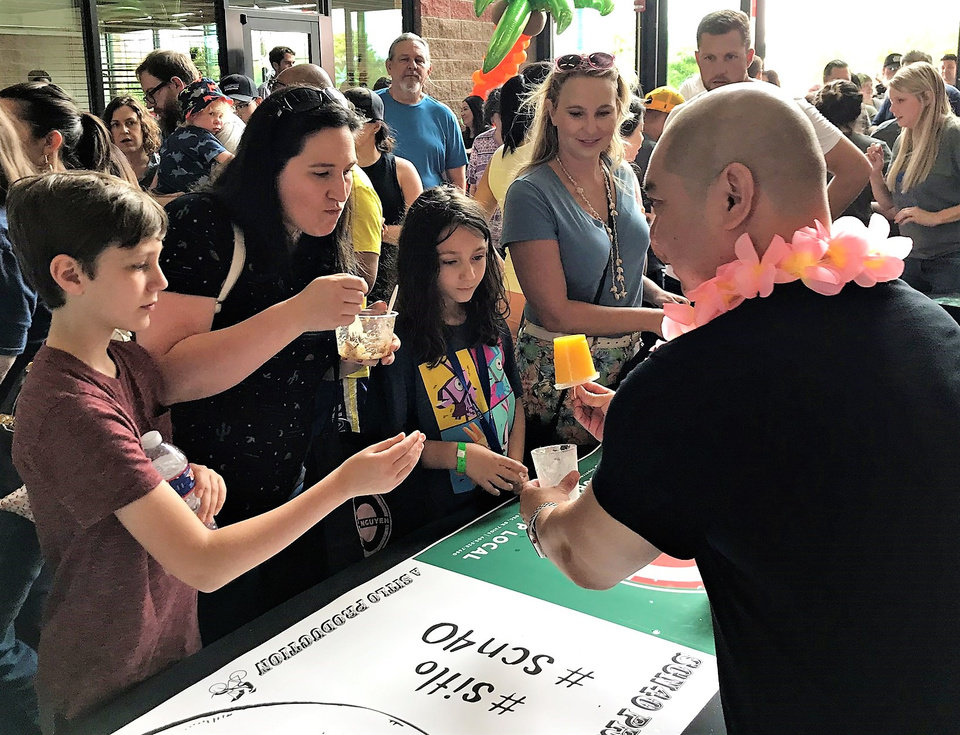 Photo - Chef Vuong Nguyen serves popsicles to the crowd at the Asian Food Fair last weekend. [Dave Cathey/The Oklahoman]