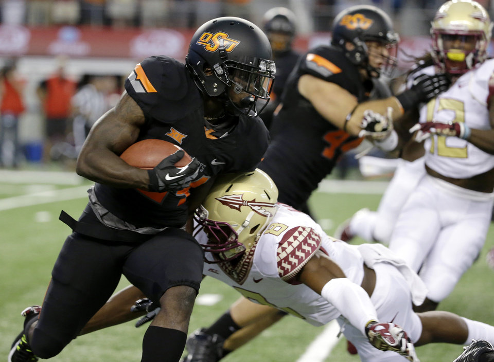 Photo - Oklahoma State wide receiver Tyreek Hill (24) looks for running room on a kickoff return as Florida State's Jalen Ramsey (8) attempts the tackle during the first half of an NCAA college football game, Saturday, Aug. 30, 2014, in Arlington, Texas. (AP Photo/Tony Gutierrez)