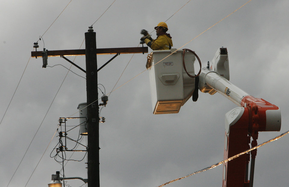 Photo - An OG&E lineman works on a tornado damaged damage power line  near Waterloo and Broadway, Tuesday , February 10, 2009.  By David McDaniel, The Oklahoman.