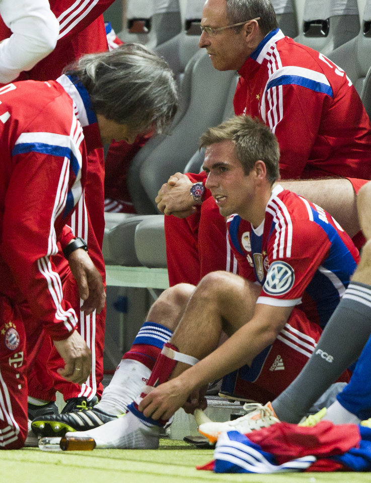 Photo - Bayern's Philipp Lahm, right, team captain of the German national soccer team, receives medical attention after he was injured during the German Soccer Cup Final between FC Bayern Munich and Borussia Dortmund at the Olympic Stadium in Berlin, Germany, Saturday, May 17, 2014. (AP Photo/Gero Breloer)
