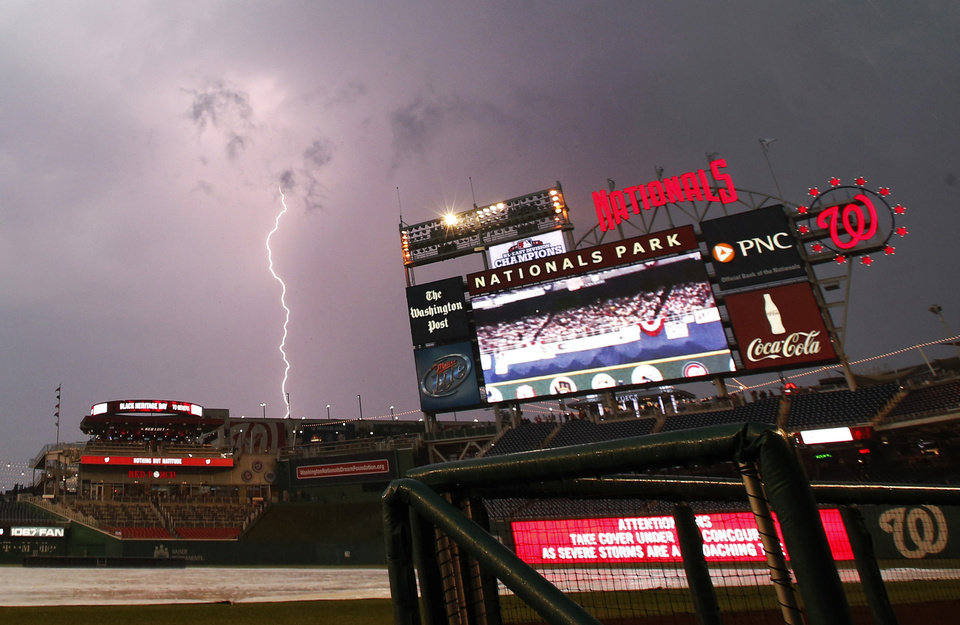 Photo - A bolt of lightening strikes down during a delayed start of a baseball game between Washington Nationals and the Miami Marlins at Nationals Park on Tuesday, May 27, 2014, in Washington. (AP Photo/Alex Brandon)