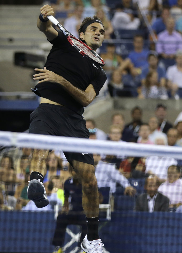 Photo - Roger Federer, of Switzerland, leaps at the net as he returns against Roberto Bautista Agut, of Spain, during the fourth round of the 2014 U.S. Open tennis tournament, Tuesday, Sept. 2, 2014, in New York. (AP Photo/Charles Krupa)