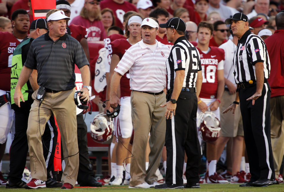 Photo - Mike and Bob Stoops protest the ejection of Jordan Evans during a college football game between the University of Oklahoma Sooners (OU) and the Louisiana Tech Bulldogs at Gaylord Family-Oklahoma Memorial Stadium in Norman, Okla., on Saturday, Aug. 30, 2014. Photo by Steve Sisney, The Oklahoman