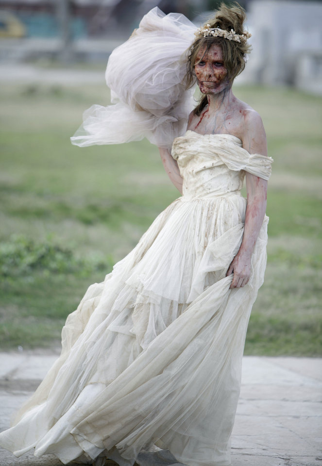 Photo - FILE - In this Dec. 5, 2010 file photo, an actress dressed as a zombie bride looks on during the filming of the movie 'Juan de los Muertos, or, 'Juan of the Dead' in Havana, Cuba.  Screenings of the film by writer-director Alejandro Brugues started the week of Dec. 8, 2011 in Havana.  (AP Photo/Javier Galeano, File)