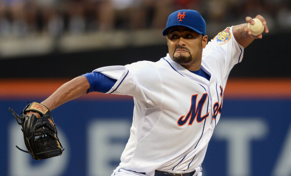 Photo - FILE - In this file photo taken Aug. 11, 2012, New York Mets' Johan Santana pitches in baseball game in New York. The two-time AL Cy Young Award winner has agreed to a minor league contract with the Baltimore Orioles, in a deal announced Tuesday, March 4, 2014,  as he tries to come back from the second major operation on his left shoulder.  (AP Photos/Henny Ray Abrams, file)