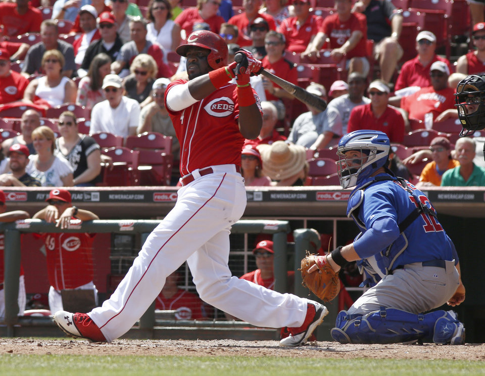 Photo - Cincinnati Reds' Brandon Phillips, left, hits a two-run double off Chicago Cubs starting pitcher Jake Arrieta in the fourth inning of a baseball game, Thursday, Aug. 28, 2014, in Cincinnati. Cubs catcher John Baker watches at right. (AP Photo/David Kohl)