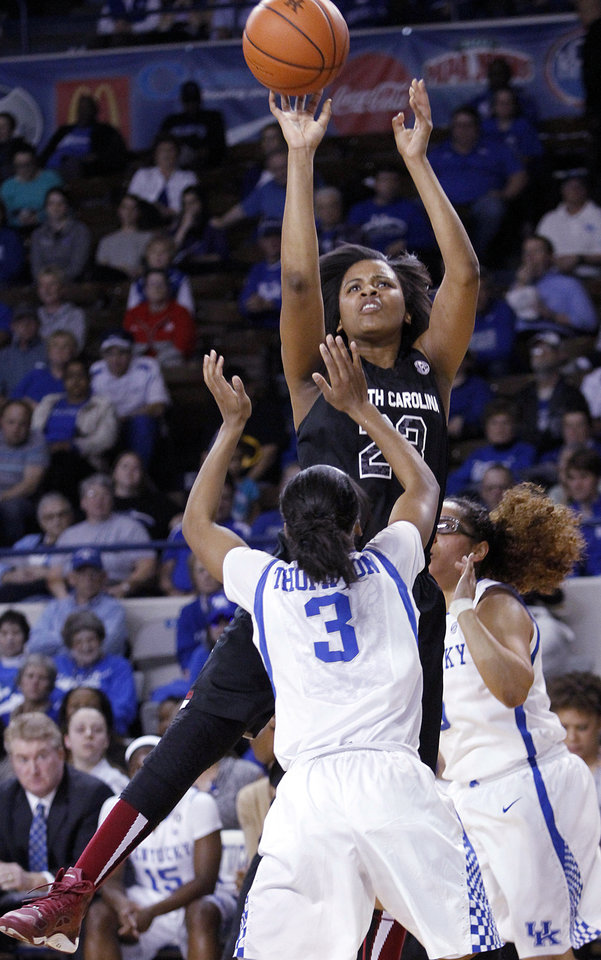 Photo - South Carolina's Tina Roy, top, shots between Kentucky's Janee Thompson (3) and Jennifer O'Neill during the first half of an NCAA college basketball game, Thursday, Feb. 20, 2014, in Lexington, Ky. (AP Photo/James Crisp)